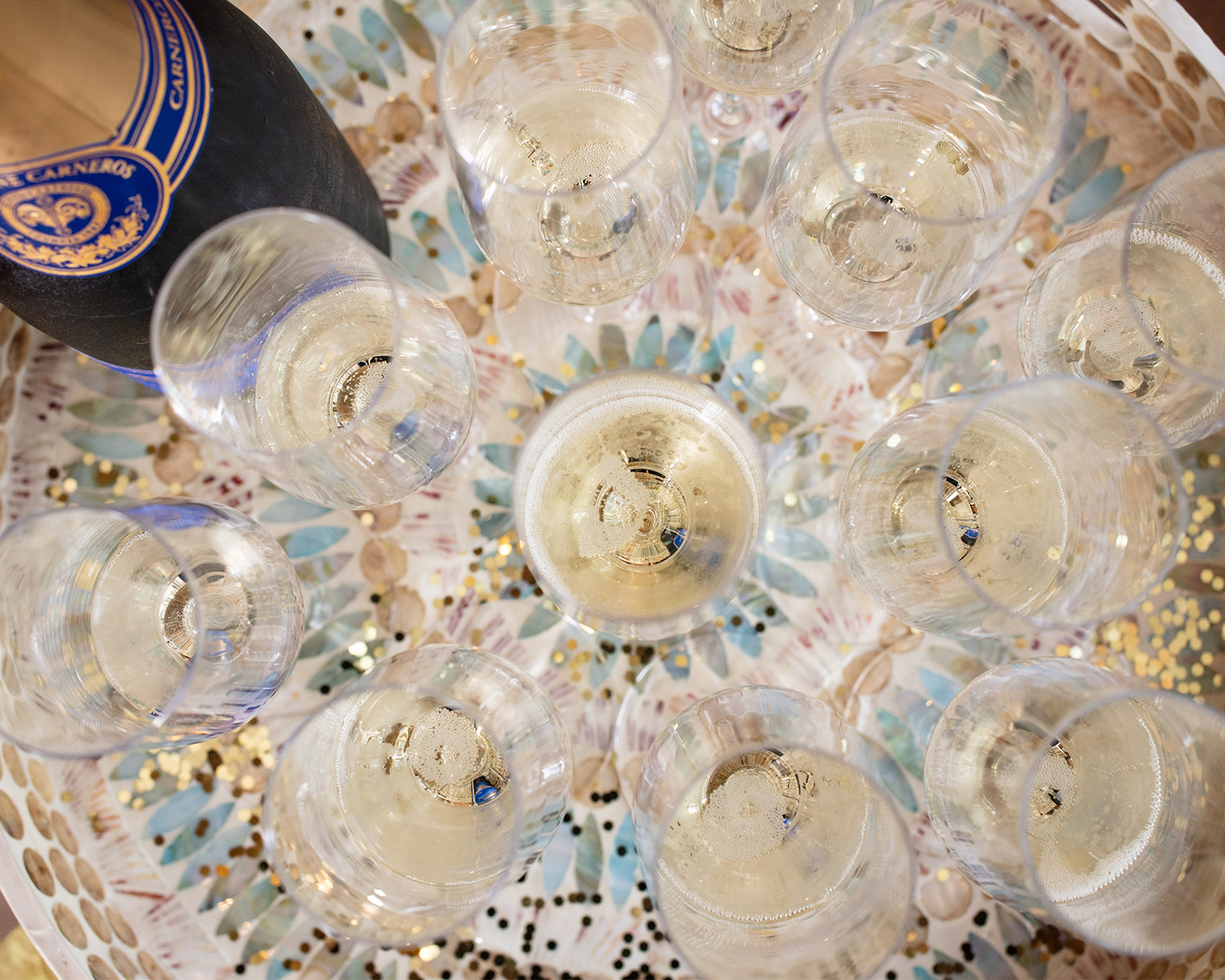 Tray of several glasses of bubbles with gold glitter